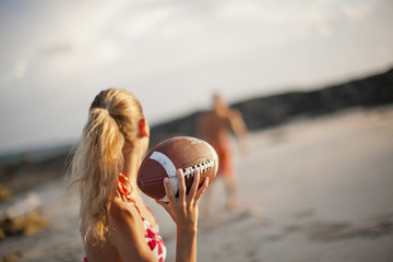 Young woman preparing to throw a football to her boyfriend on a sandy beach.