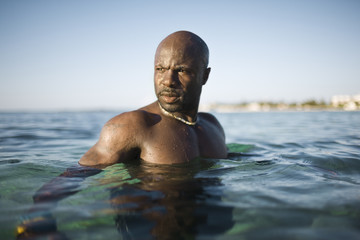 Muscular man swimming in the sea.
