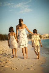 Mother and two children walking along the beach.