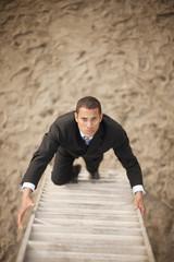 Businessman climbing ladder on beach