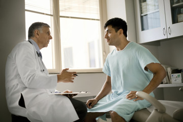 Senior doctor consulting with a patient after a medical exam.