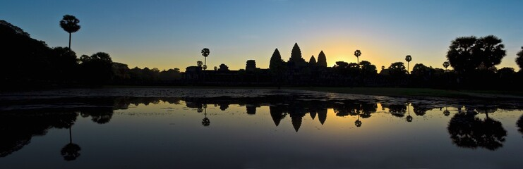 Silhouette of ancient ruins, reflected in water at sunset.
