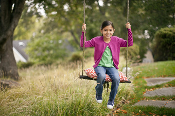 Happy young girl sitting in a swing.