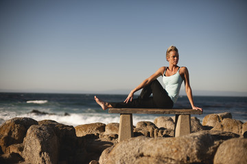 Woman doing yoga on the rocks of the beach.