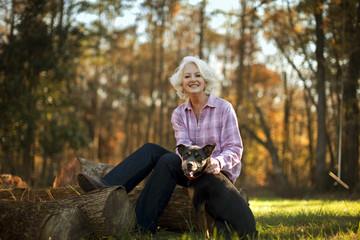 Woman sitting on log with dog.