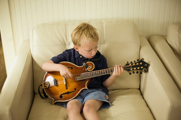 Young boy sitting in an armchair plays a small acoustic eight-string guitar.