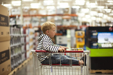 Bored young boy stares as he sits in the top basket of a metal shopping trolley in a large store.