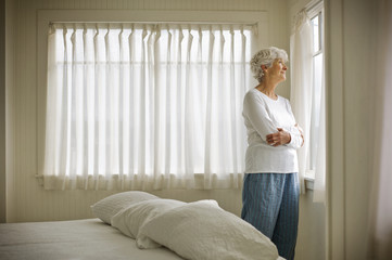 Elderly woman looking through bedroom window.