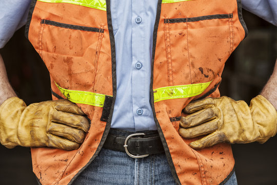 Close-up of landscape company worker wearing work gloves and safety vest