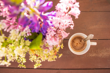 top view image of colorful summer flowers next to cup of coffee on wooden table. vintage.morning breakfast concept