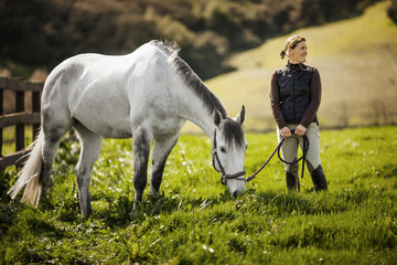 Mid adult woman standing with her horse in a green pasture.