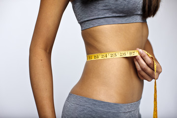 Close up of young kickboxer measuring her toned stomach.