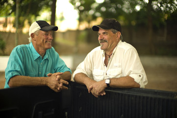 Two farmers smile and talk as they lean on the bed of a truck.