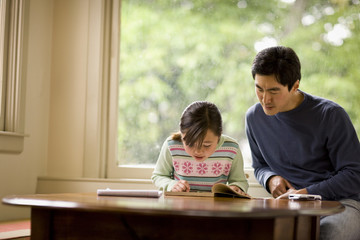 Father helping his daughter with her homework.