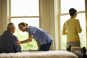 Female nurse smiles and leans down to put a reassuring hand on the arm of a man sitting on a bed while a woman stands looking out of a bedroom window.