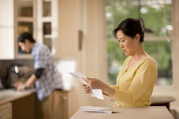 Woman reading her bills looking worried.