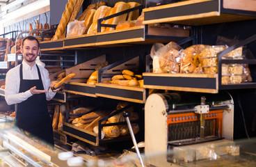 Male shop assistant demonstrating delicious loaves of bread in bakery