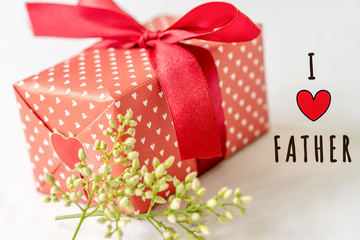 Happy father's day concept. Gift box and flower, paper tag with I LOVE FATHER text