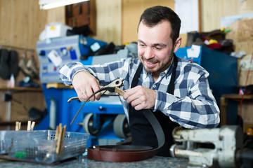 Male worker shaping new hole in belt