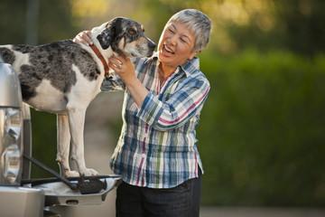 Happy senior woman bonding with her dog.