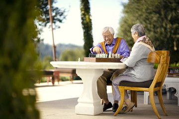 Happy senior couple playing a game of chess.
