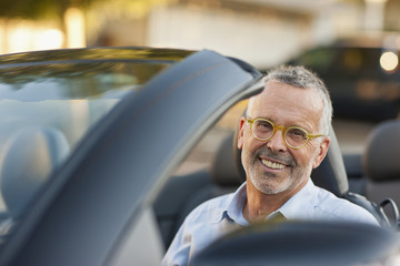 Portrait of a smiling middle aged man sitting in a car.
