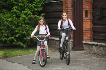 Happy young girls riding on bicycles from home to school