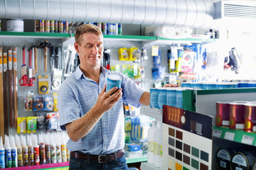 Portrait of male customer selecting paint can in housewares department