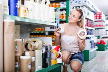 happy woman customer choosing adhesive tape in household store
