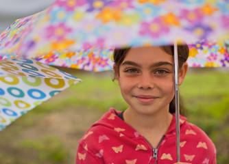 Portrait of girl holding open umbrella.