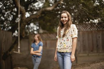 Two teenage girls in a backyard.