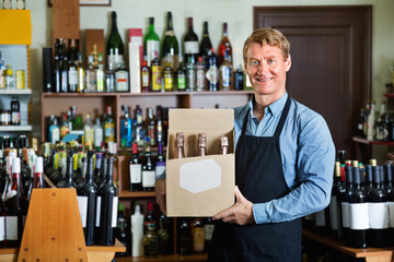 Man seller wearing apron having package box with wine bottles