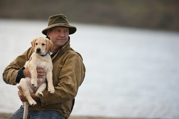 Portrait of man on beach holding a puppy.