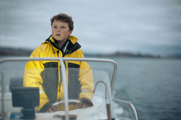 Pre-adolescent boy steers a boat.