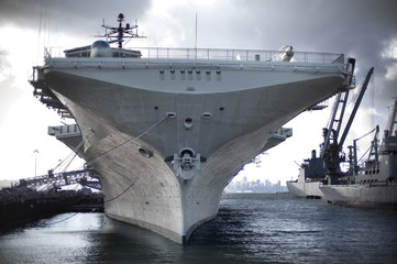 Military ship resting in a commercial dock.