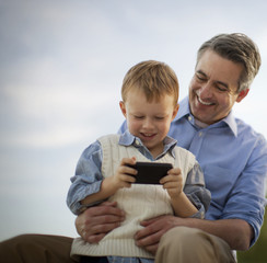 Mature man shows his young son his mobile phone.