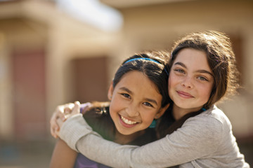 Two smiling girls hugging.