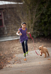 Girl running with puppy.