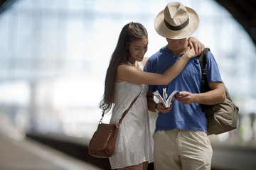 Young woman smiles and hugs a young man as they read a guidebook while waiting on the platform of an arched railway station.