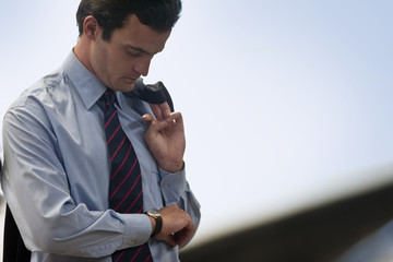 Businessman checks the time on his wristwatch.