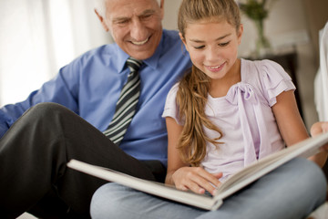 Senior man and his young granddaughter smile as they sit on the floor and read a book together.