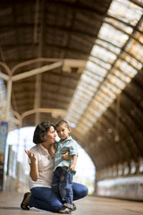 Thirtysomething mother and her son at a railway station.