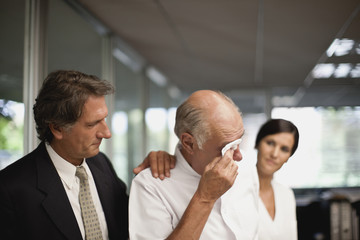 Senior businessman is comforted by a male and female colleague as he wipes tears from his eyes.