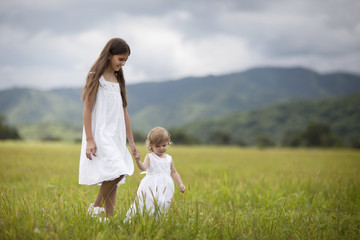 Girl and her younger sister wearing white sun dresses walk through a field.