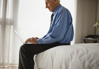 Senior businessman working on his laptop from home.
