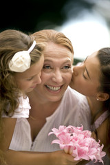 Two young girls kiss their grandmothers' cheeks.