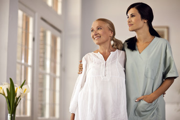 Female nurse standing with her arm around senior female patient as they look out window.