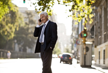 Mature business man listening on cell phone on city street.