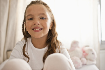 Portrait of young girl sitting on her bed.