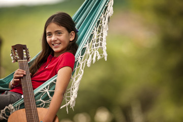 Girl resting in hammock with her guitar.